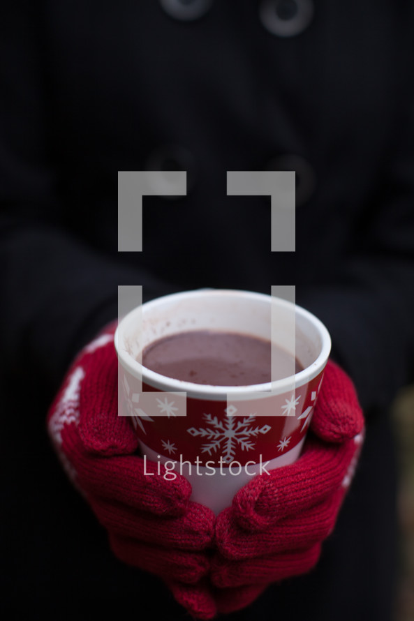 Hands wearing red mittens holding a cup of hot chocolate in a Christmas cup.