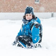 a boy in a winter coat sitting in falling snow