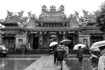 People walking with umbrellas towards a temple
