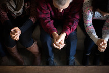People sitting on a couch bowed in prayer