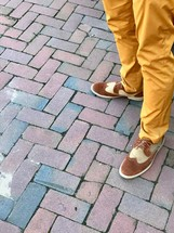 a man in dress shoes standing on brick pavers