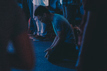 kneeling in prayer and surrender at a worship service