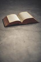 an open Bible on a floor