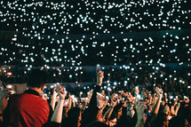 cellphone lights in a crowd at a concert