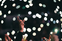 cellphones taking pictures of bokeh lights at a concert