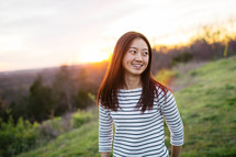 An Asian girl walking in a meadow at sunset