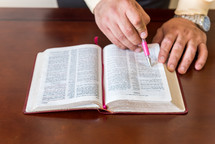 man reading a Bible and pointing