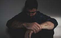 a man sitting alone praying