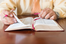 Hands holding a pen turning pages of a Bible.