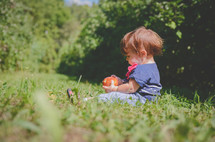 a toddler sitting in grass holding an apple