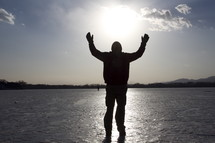 Silhouette of man with arms raised praising God while walking on ice over a frozen lake.