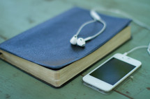 Iphone on a wooden table with earbuds on a closed Bible.