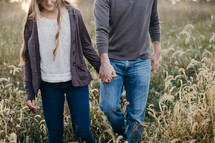 a young couple holding hands walking through a field of tall grass