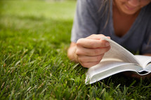 a person sitting in the grass reading a Bible