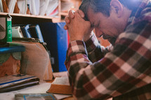 a man sitting at his desk praying and reading a Bible