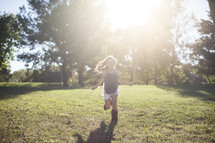 a happy child running outdoors in the grass and sunlight.