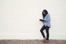 young woman standing reading a Bible