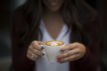 a young woman holding a cup of coffee with creamer
