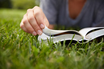 a person sitting in the grass reading a Bible.