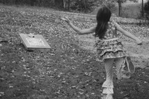 a child throwing a bean bag for corn hole