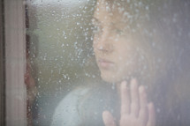 Girl looking out a frosted window pane.