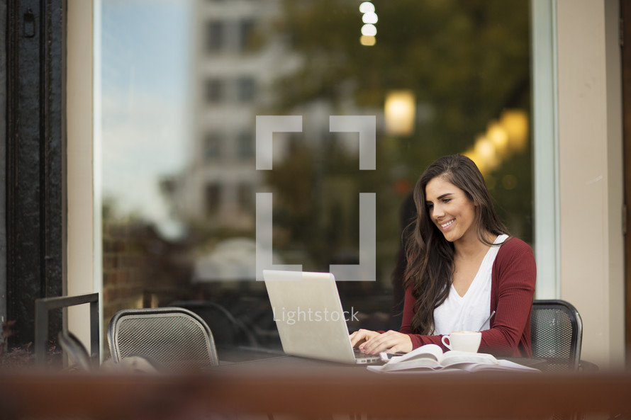a young woman sitting at a table outdoors working at a laptop computer