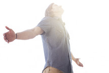 a man standing with outstretched arms enjoying the sunshine.