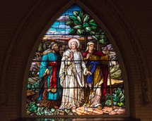 A stained glass window depicting Jesus and his disciples.