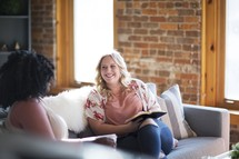 women's group sitting on a couch drinking coffee and reading Bibles