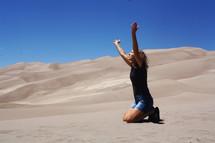 a woman kneeling in sand