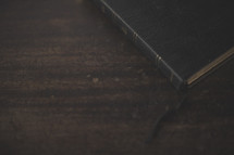 The edge of a bible and bookmark on wood