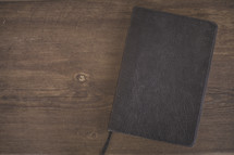 A closed Bible on wood