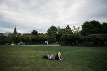 a man lying in the grass reading