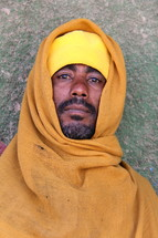 Ethiopian Orthodox Eunuch man wearing a yellow robe [For similar search Ethnic Face Smile]