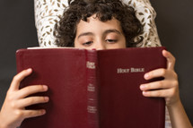 Boy reading the Bible.