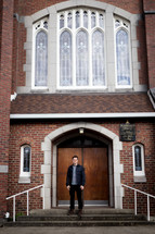 a man standing in front of church doors