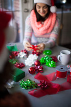 A woman in a santa hat smiling and wrapping Christmas presents