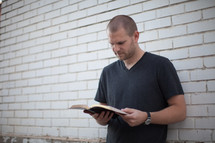 a young man reading a Bible standing in front of a white wall