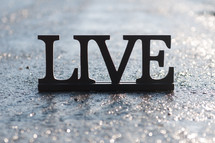 "Letters spelling ""live"" on wet pavement."