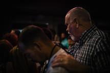 Men praying at a church service.