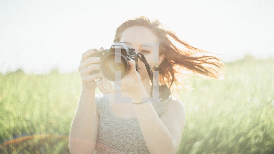 a teen girl holding a camera in a field