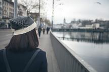 woman walking down a sidewalk near a canal