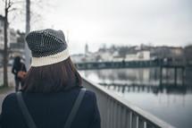 woman walking down a sidewalk by a canal