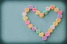 candy conversation hearts for Valentine's day on a table in the shape of a heart