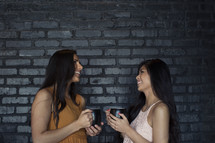 Two young women holding coffee cups and smiling at each other.