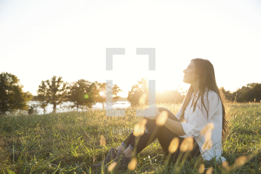 woman sitting in grass and looking up.