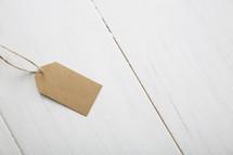 A brown paper gift tag on a white table.