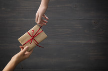 One person giving a wrapped gift to another.