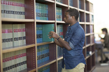 a man looking at books in a library