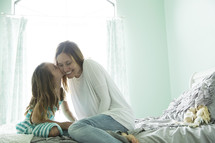 a mother and daughter talking on a bed